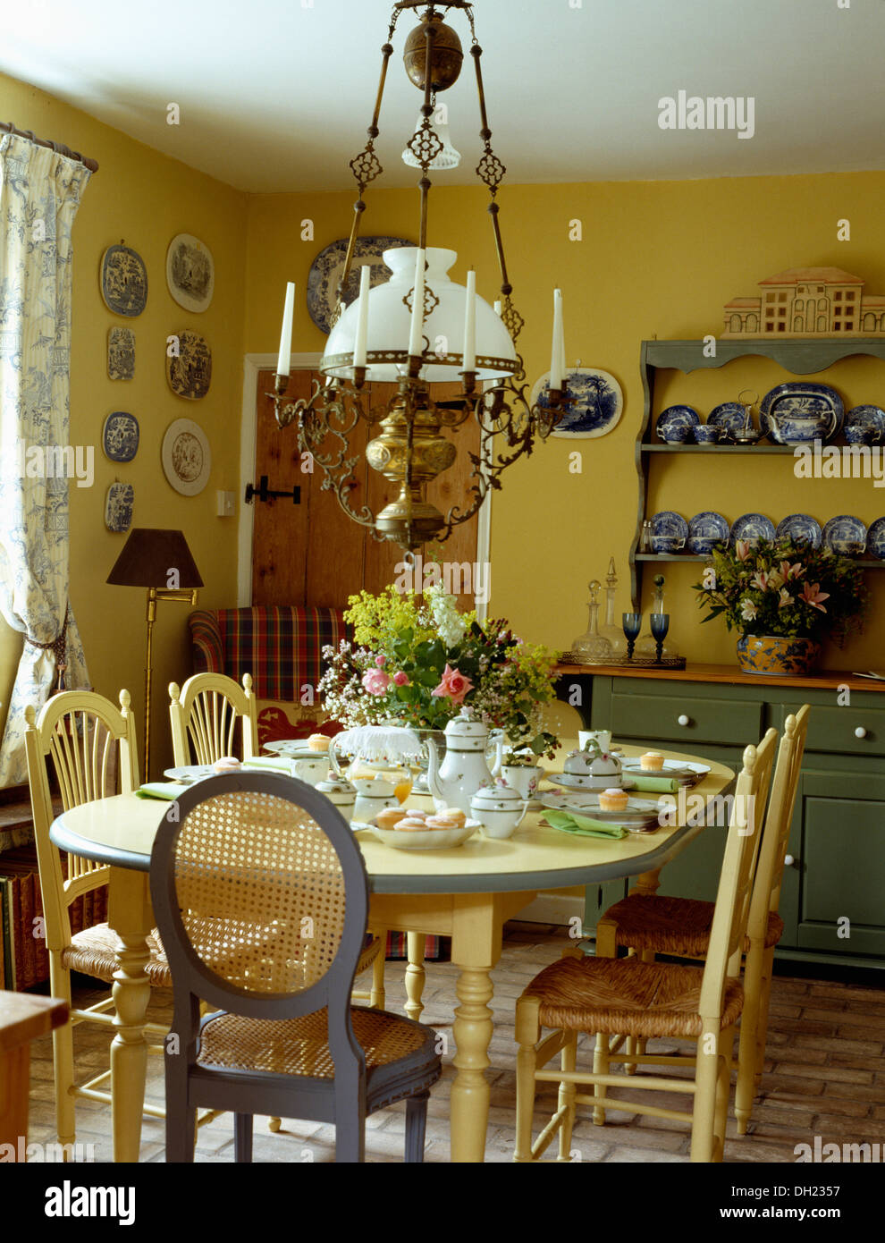 Glass Brass Victorian Lamp Above Cream Chairs And Table Set For Lunch In Pale Yellow Cottage Dining Room With Green Dresser