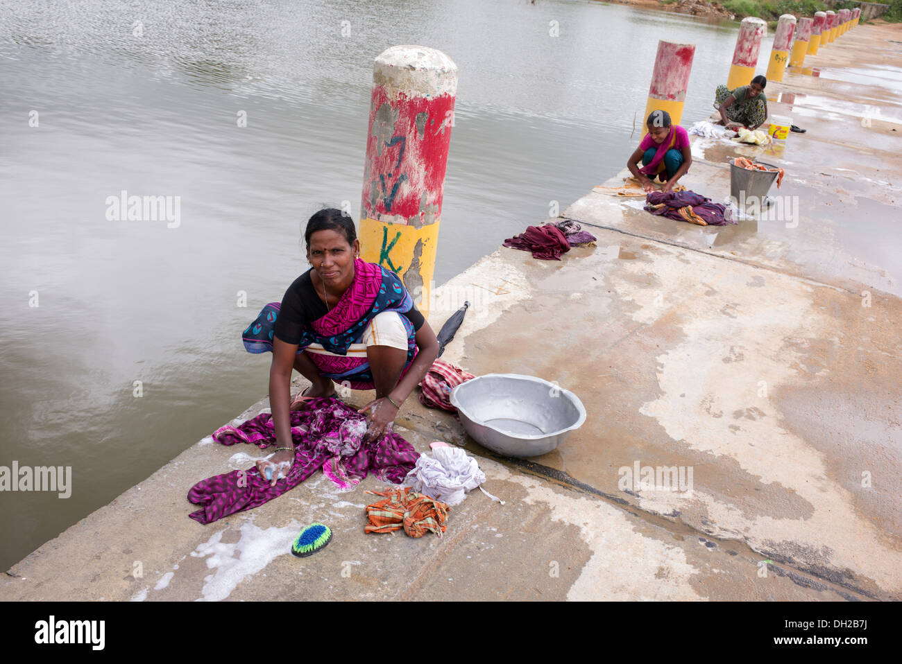 Indian women washing clothes by hand next to a river ...