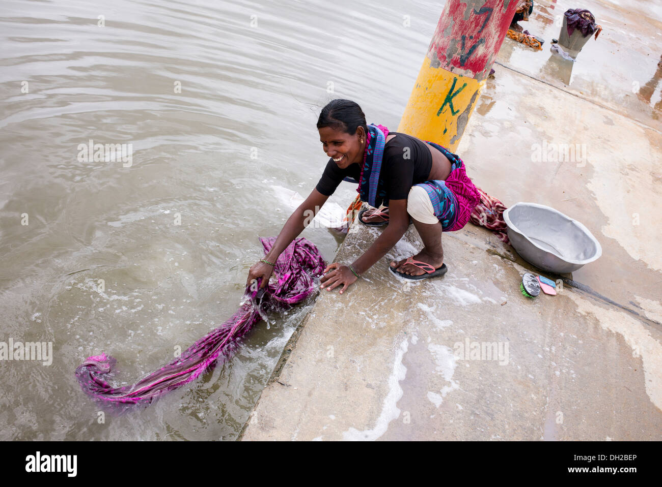 Indian woman washing clothes by hand next to a river ...