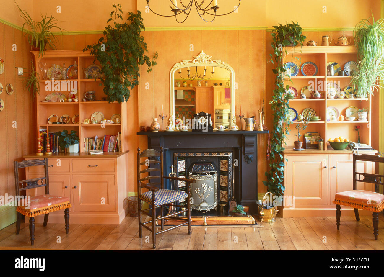 Antique Chairs And Painted Dressers On Either Side Of Black Victorian Fireplace In Pale Orange Dining Room With Wooden Flooring