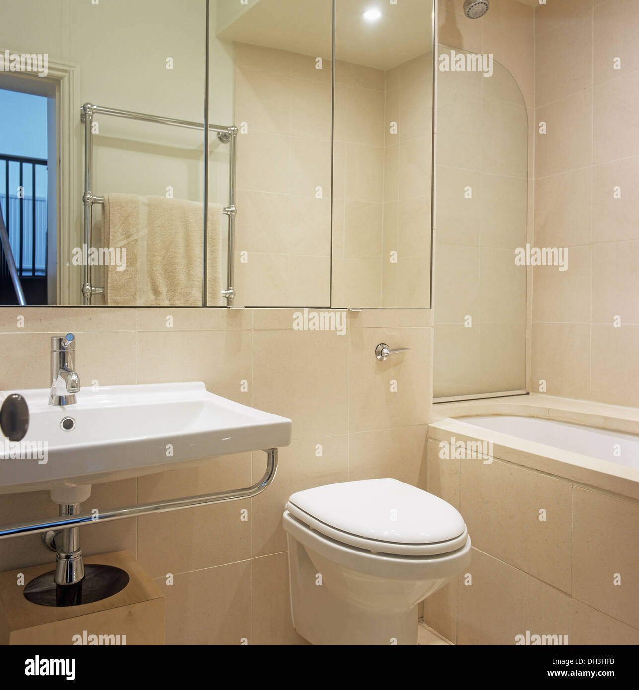 Mirror Cabinet Above Rectangular Basin And Wall Mounted Toilet In Modern  Tiled Bathroom With Under Set Bath