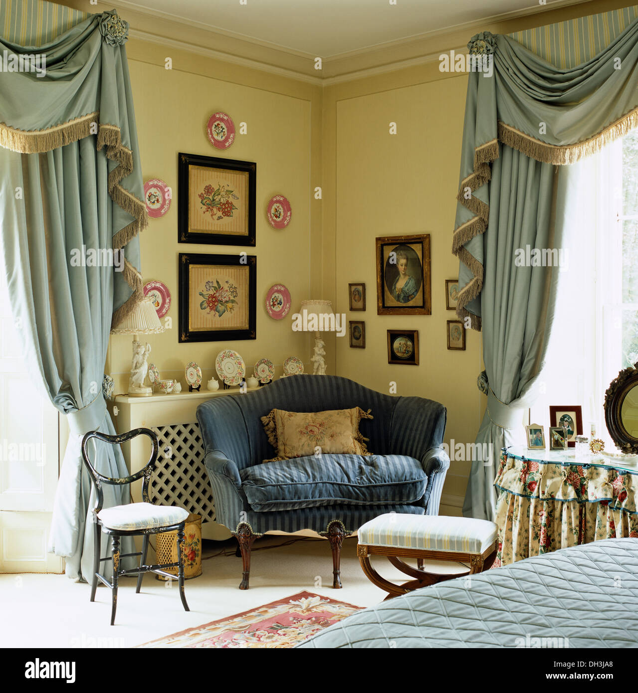 Small blue sofa in corner of country bedroom with pale blue silk  swagged tailed curtains. Small blue sofa in corner of country bedroom with pale blue silk