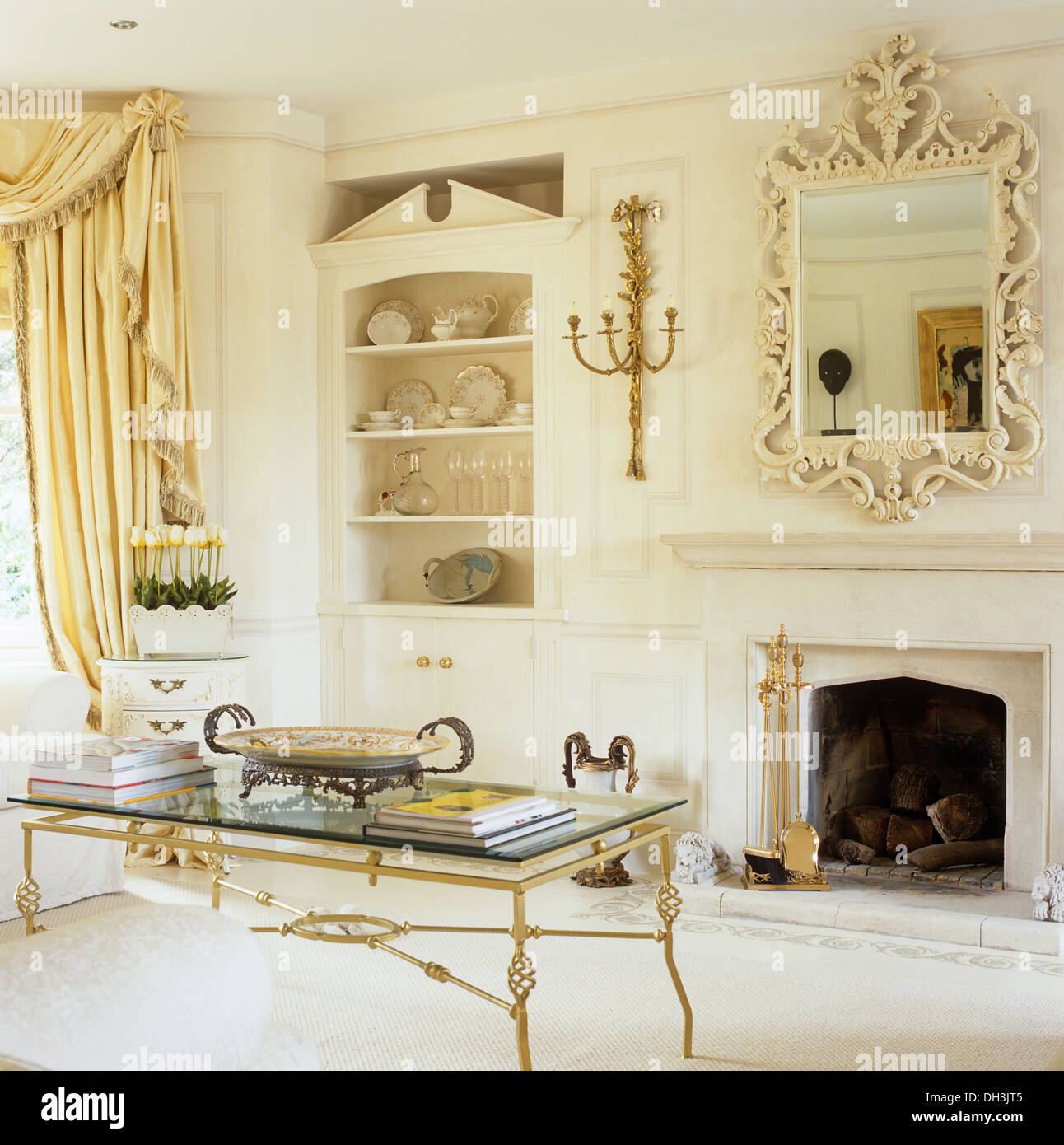 Glass Topped Gold Coffee Table In Front Of Fireplace In Traditional Drawing  Room With Alcove Shelves And Silk Drapes