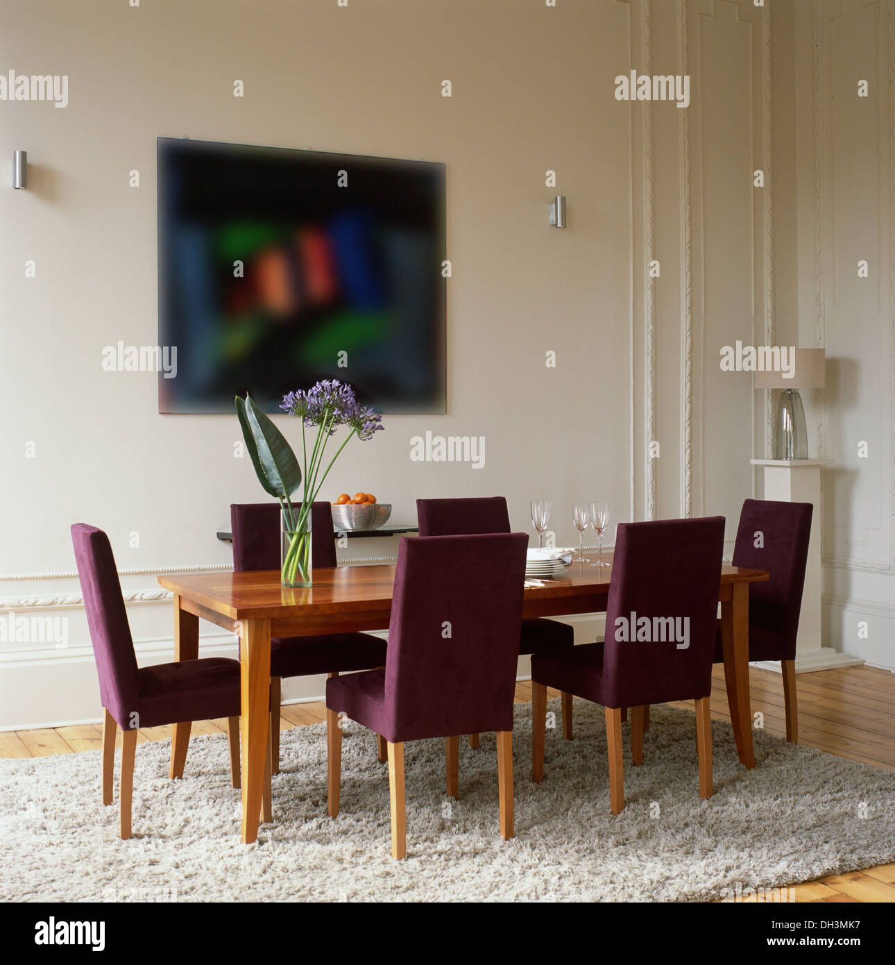 Purple Upholstered Chairs At Plain Wood Table In Modern Dining Room With White Shag Pile Rug On Wooden Flooring
