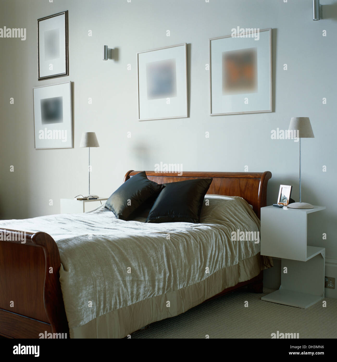 lamps on modern white cantilevred tables on either of sleigh bed with cream crushed velvet bed
