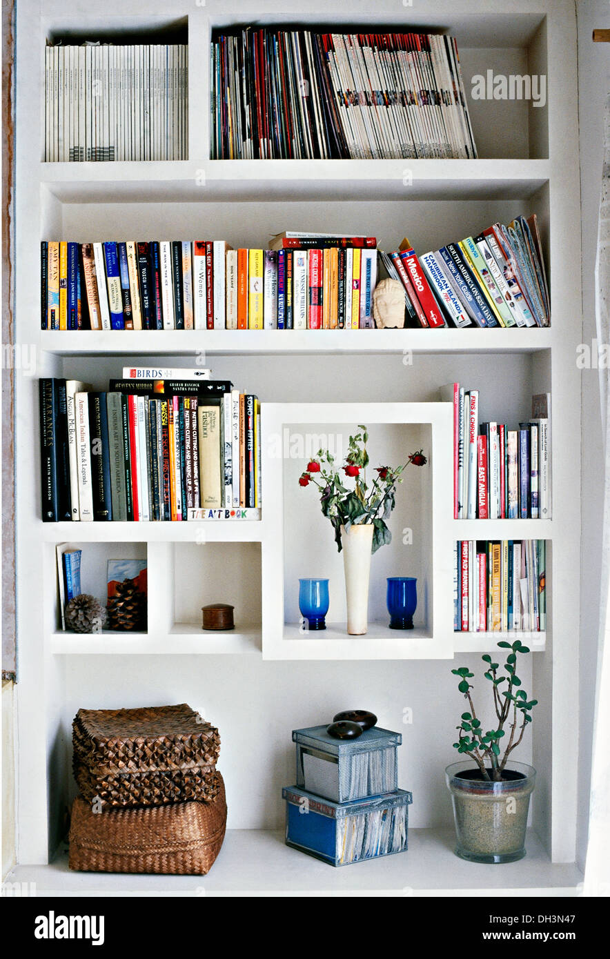 Close-up of white painted shelves with books and wicker storage ...