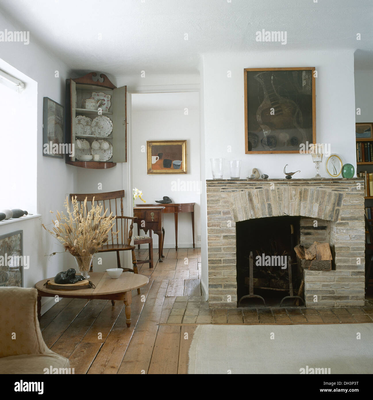 large painting above brick fireplace in open plan cottage living