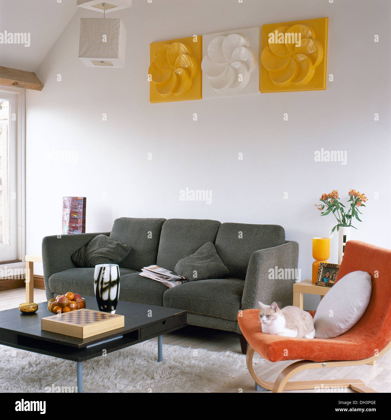 Plastic Wall Art Above Gray Sofa In Modern Living Room With Black Coffee Table And Orange Canti Levered Chair On Shag Pile Rug