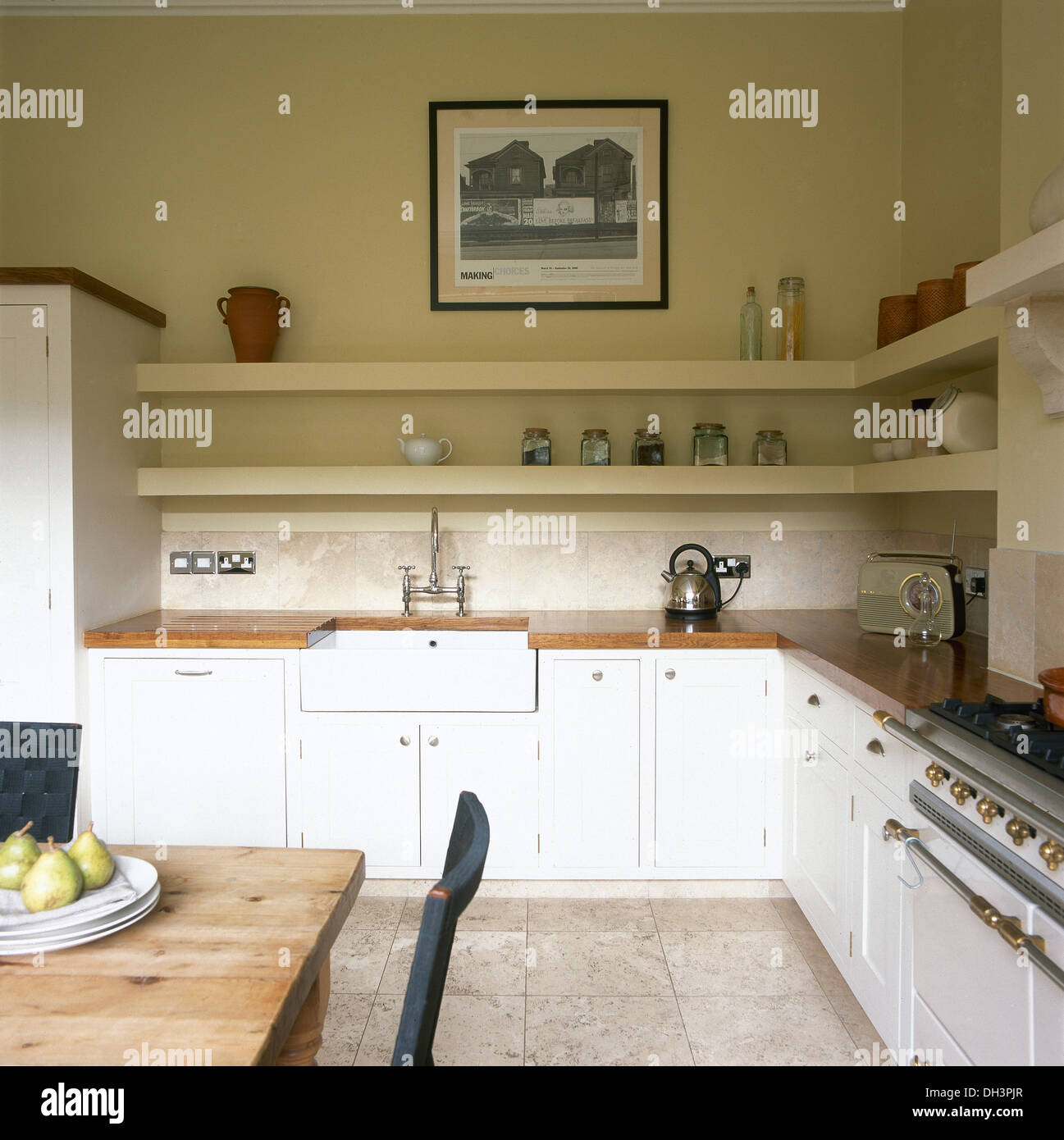 Framed Photograph Above Simple Shelving And Belfast Sink In Country Kitchen With White Painted Units Plain Wood Dining Table