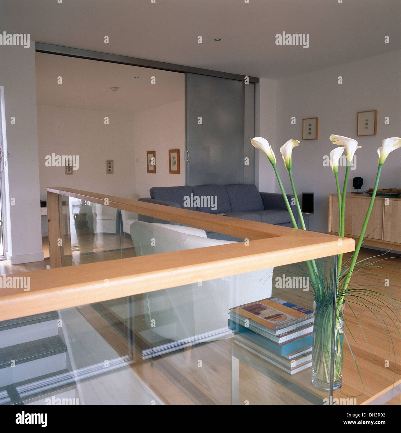 White Arum Lilies On Table Beside Glass Half Wall In Modern Open Plan Living Room