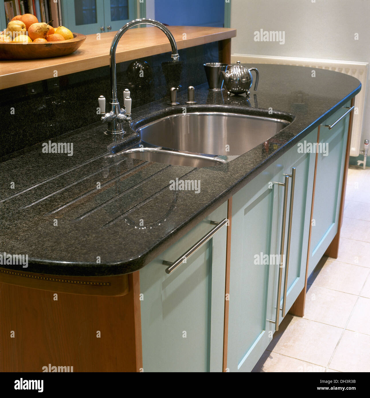 Chrome tap above under set stainless steel sink in pale blue ...