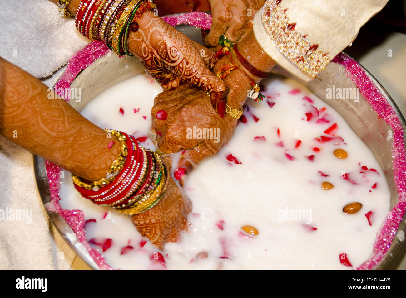 Indian wedding ceremony Bride and Groom searching for ring in pot ...