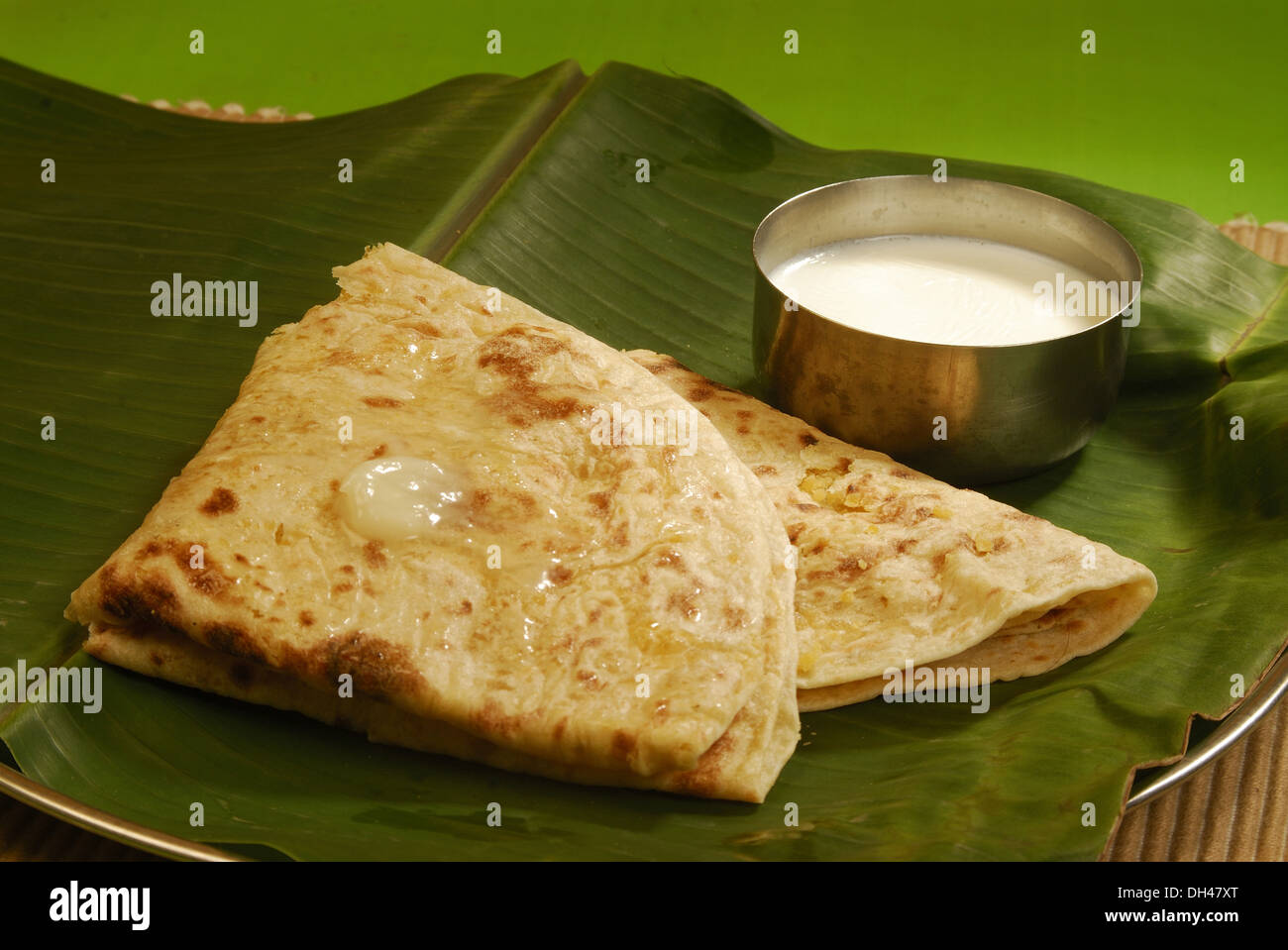 Indian Food Sweet Puran Poli With Ghee And Milk Served On Green Banana Leaf