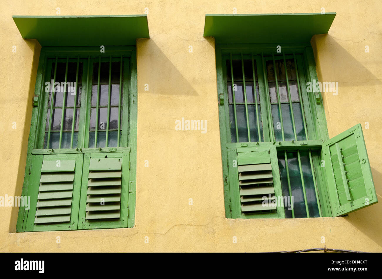 Stock photo green painted wooden windows yellow painted wall of house kolkata west bengal india