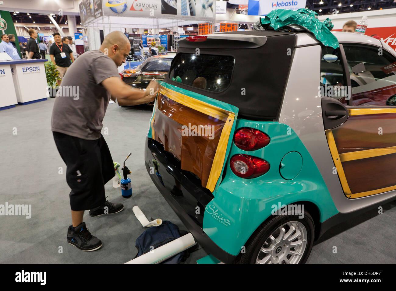 Technician Installing Vinyl Car Wrap On Smartcar Stock Photo