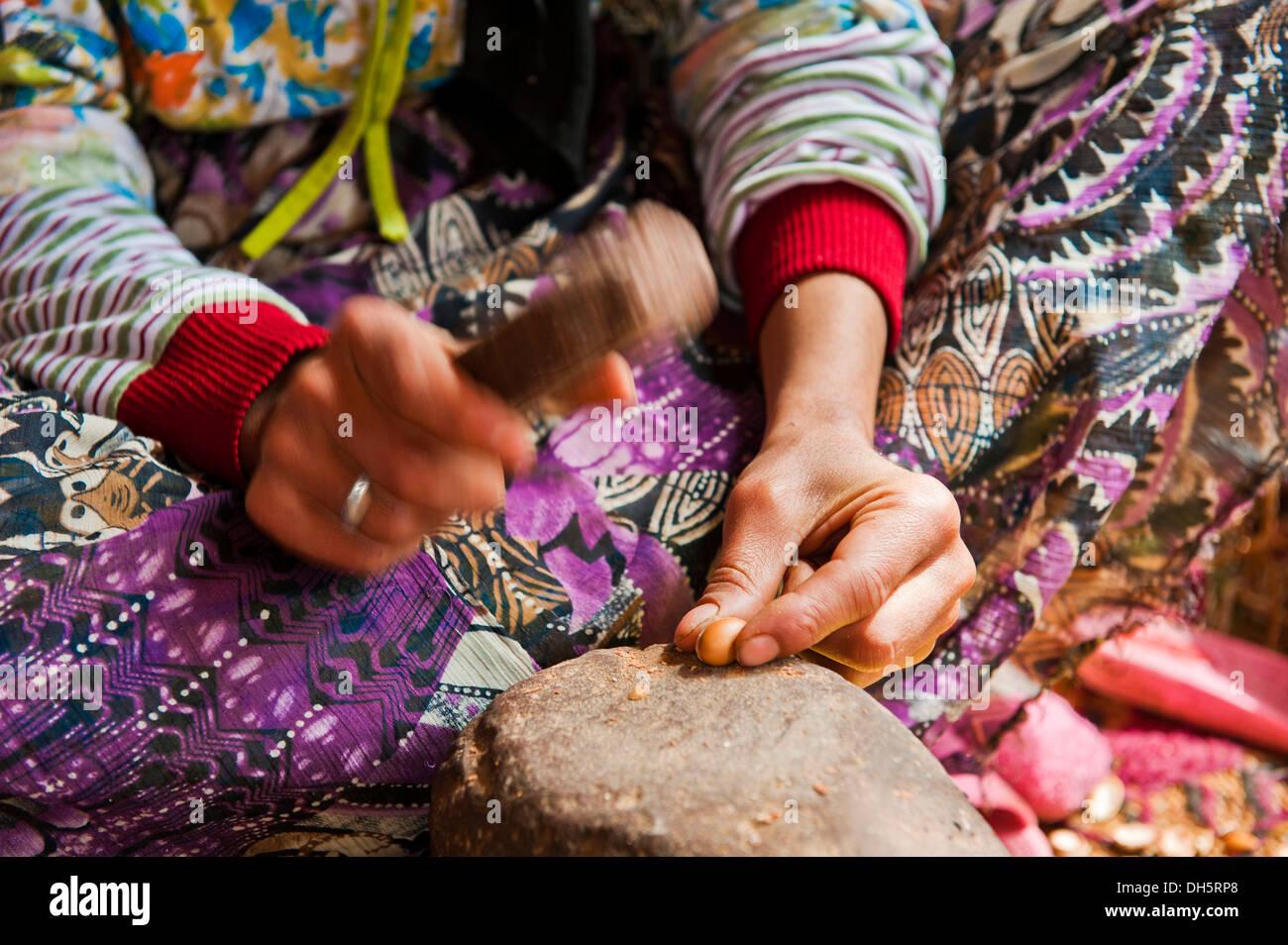 berber-woman-hitting-argan-nuts-on-a-sto
