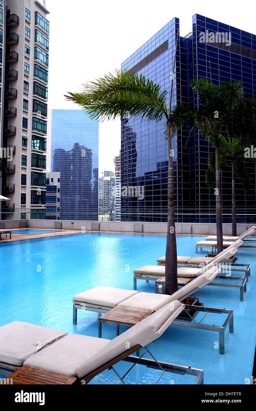 Lounge chairs by swimming pool in condominium high rise building with stock photo royalty free for Houston swimming pool high rise