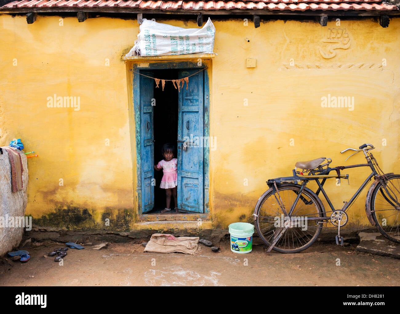 Small indian girl standing in her rustic village house doorway andhra pradesh india