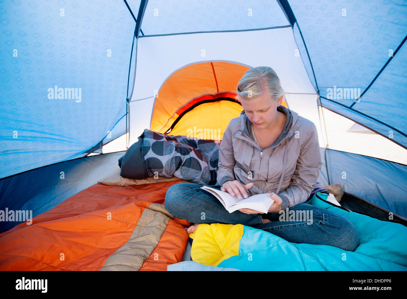 A Young Woman Reading A Book Inside A Tent; California United States Of America & A Young Woman Reading A Book Inside A Tent; California United ...