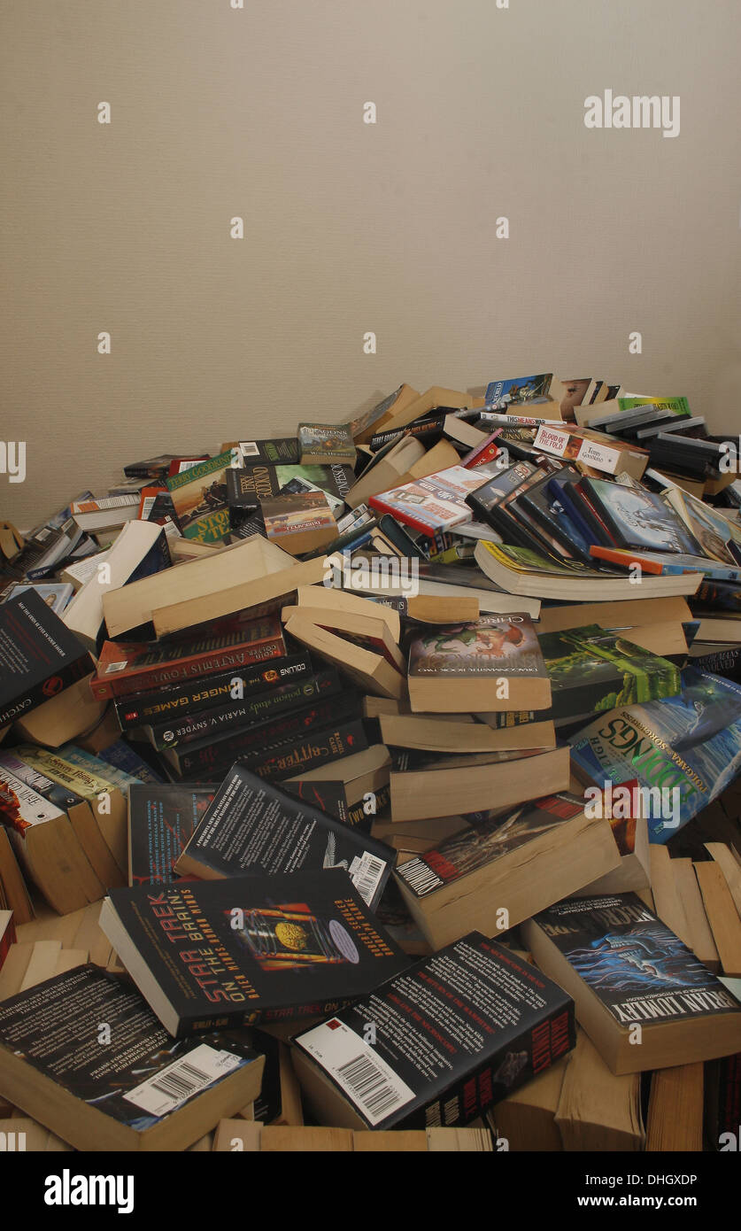 Large pile of books and DVDs on floor of house Stock Photo