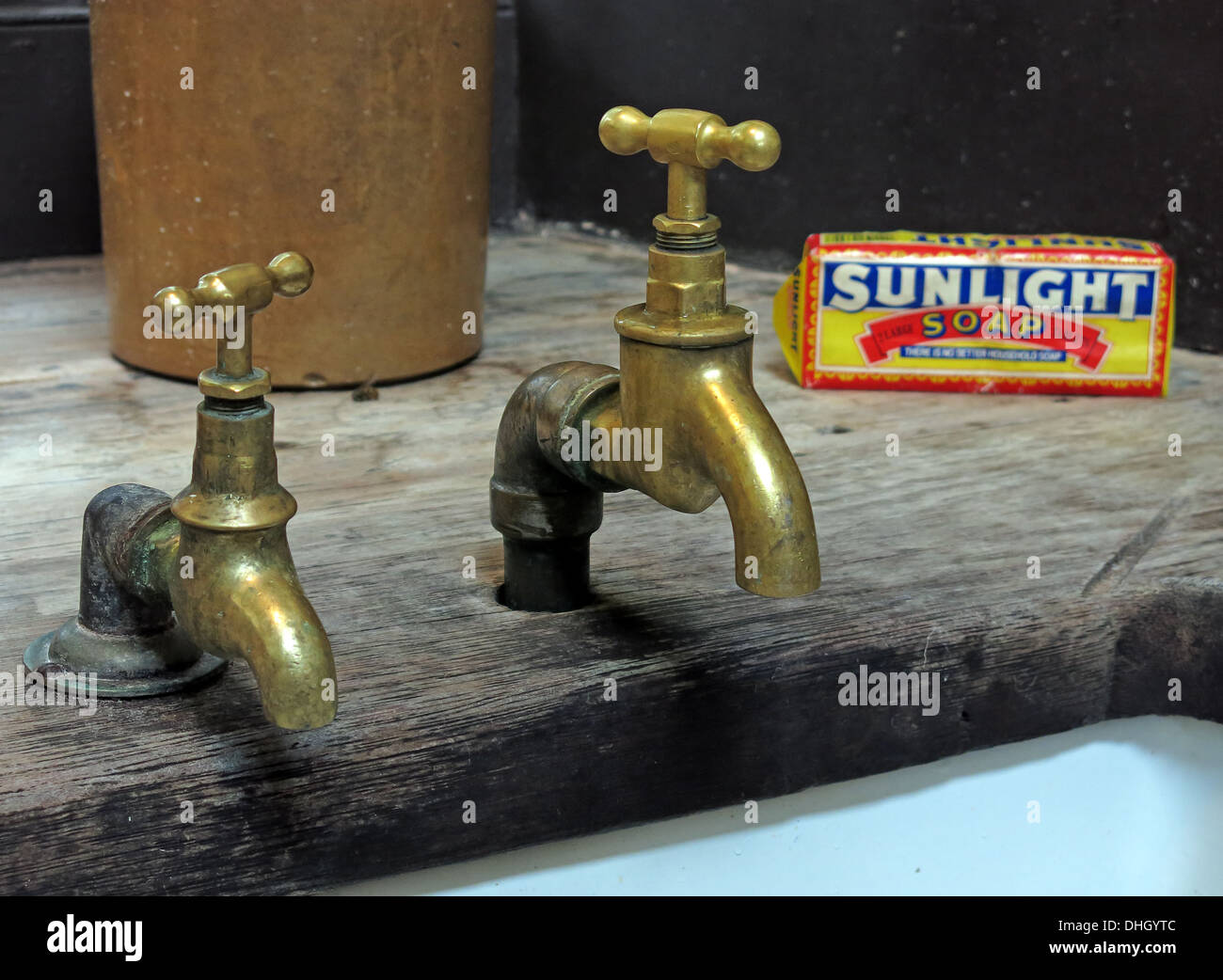 Two old historic Victorian brass taps, Lever Sunlight soap over a ...