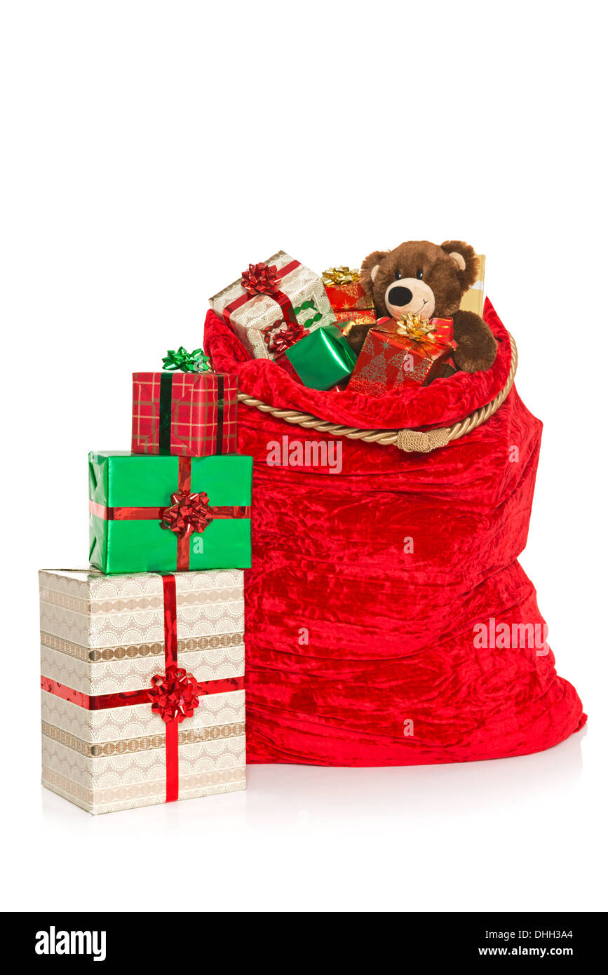 A red christmas sack full of gift wrapped presents and toys a red christmas sack full of gift wrapped presents and toys isolated on a white background negle Choice Image