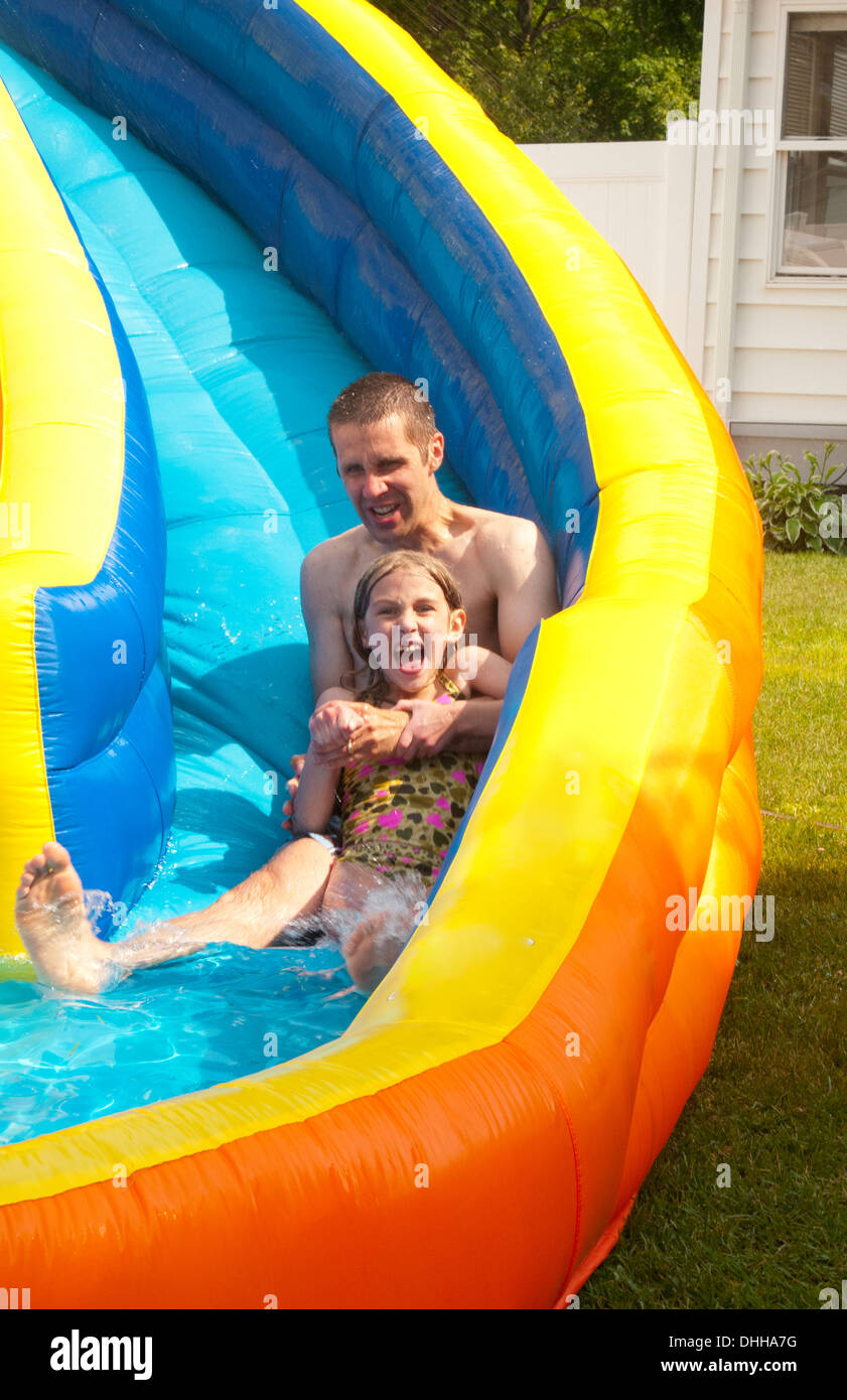 family water slide in back yard at home with water in summer with