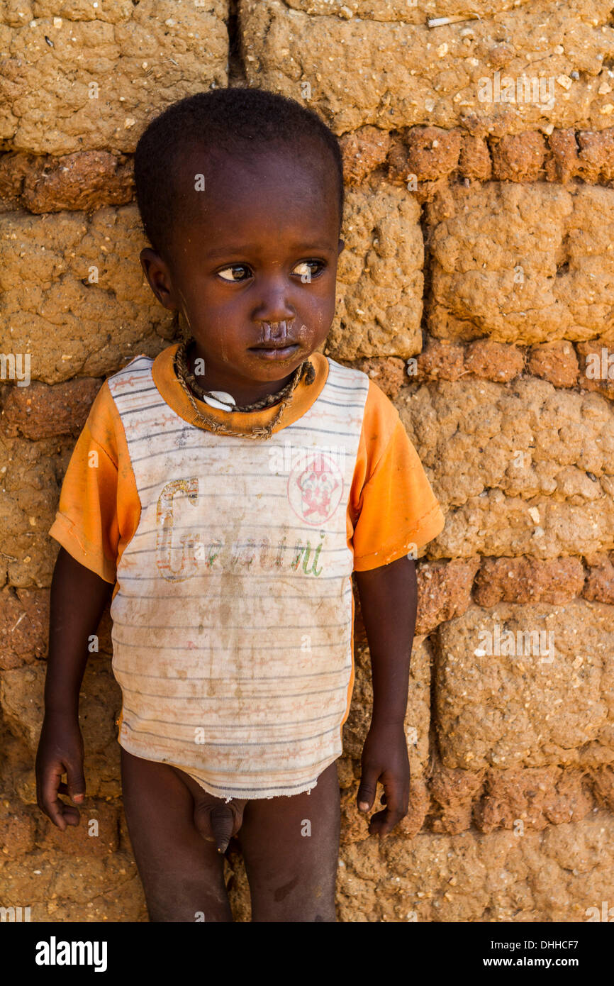 child naked  Young Fulani child in ragged clothing, half-naked poses by a traditional  house near Kaduna, Nigeria. Fulanis are traditionally nomadic people, ...
