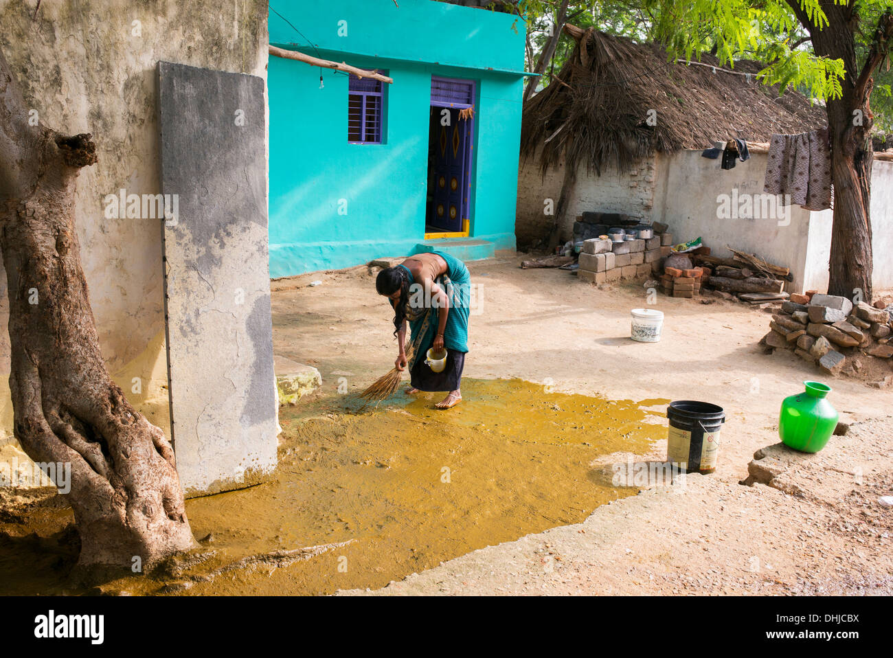Indian custom of a woman spreading watered down cow dung ...