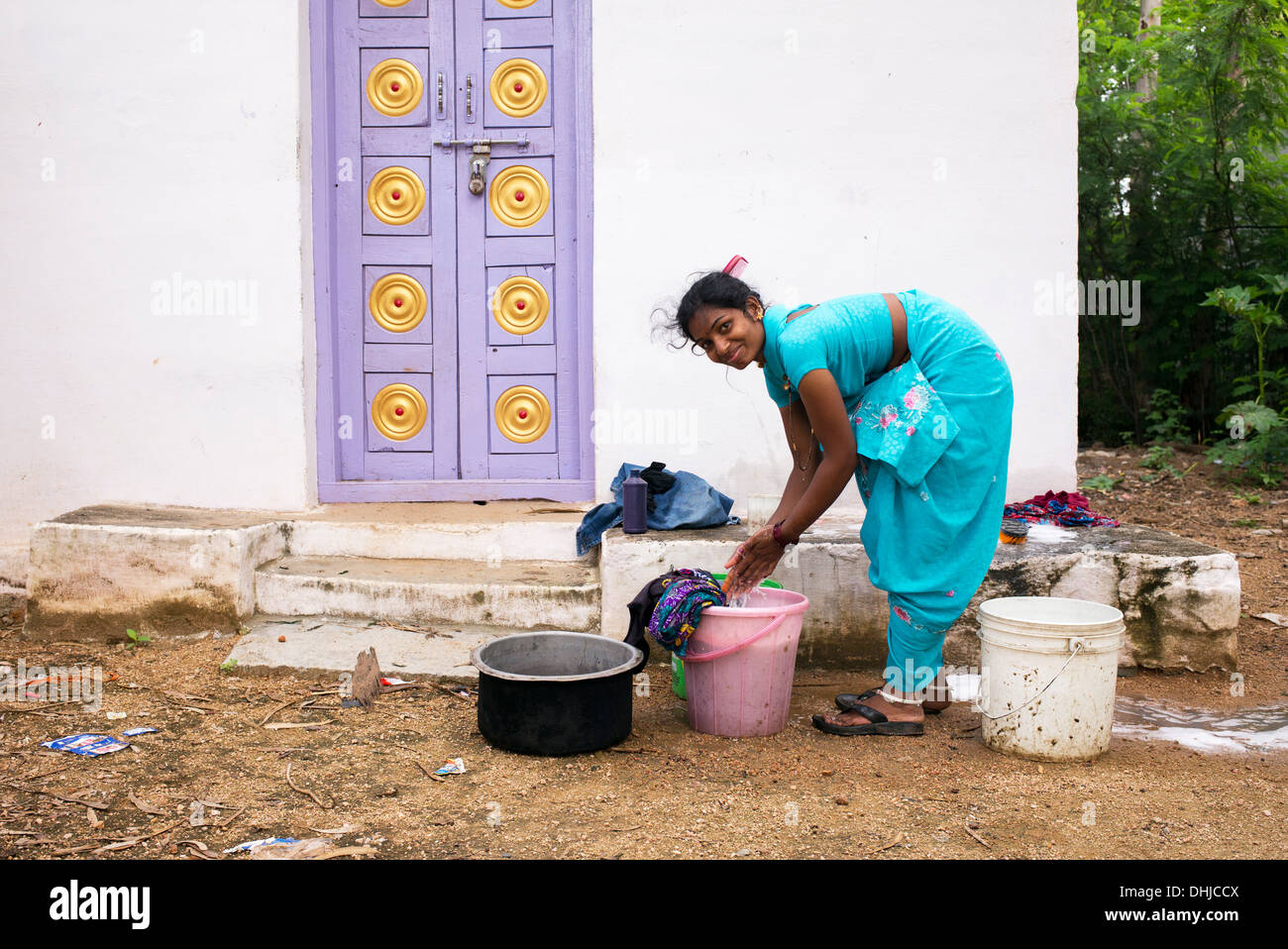 indian woman washing clothes outside her home in a rural indian stock photo royalty free image. Black Bedroom Furniture Sets. Home Design Ideas