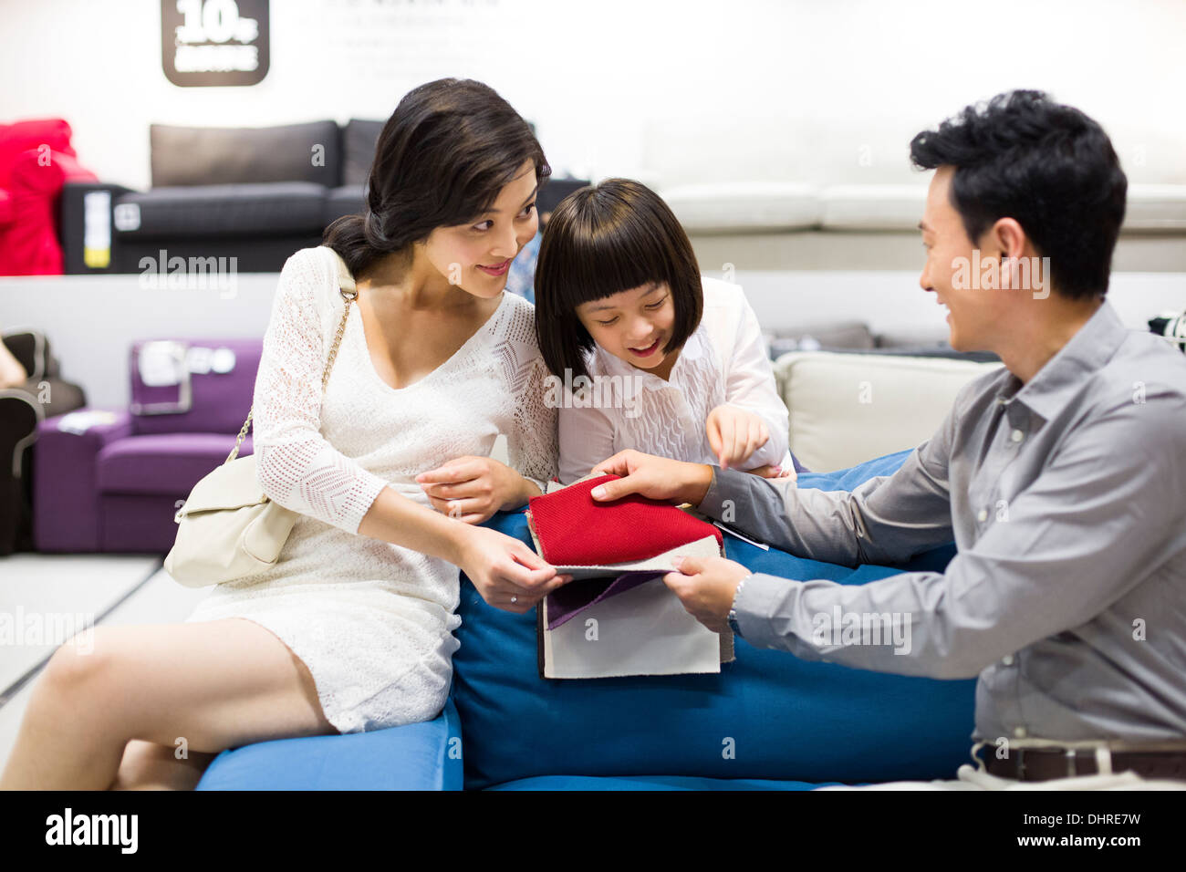 Happy family shopping for sofa in furniture shop Stock