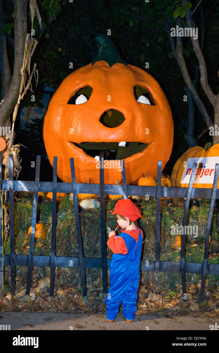 Toddler Dressed Up as Mario fStanding next to Giant Jack-O-Lantern ...