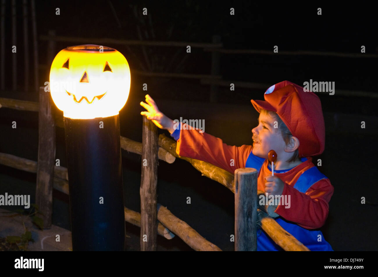 Toddler Dressed Up as Mario Reaches toward Jack-O-Lantern on Lamp ...