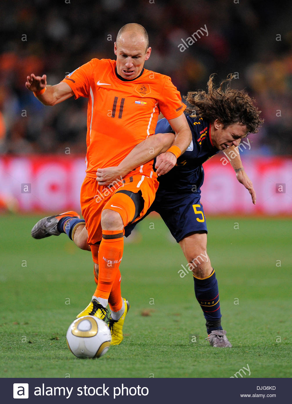 Arjen Robben of Netherlands tangles with Carles Puyol of Spain