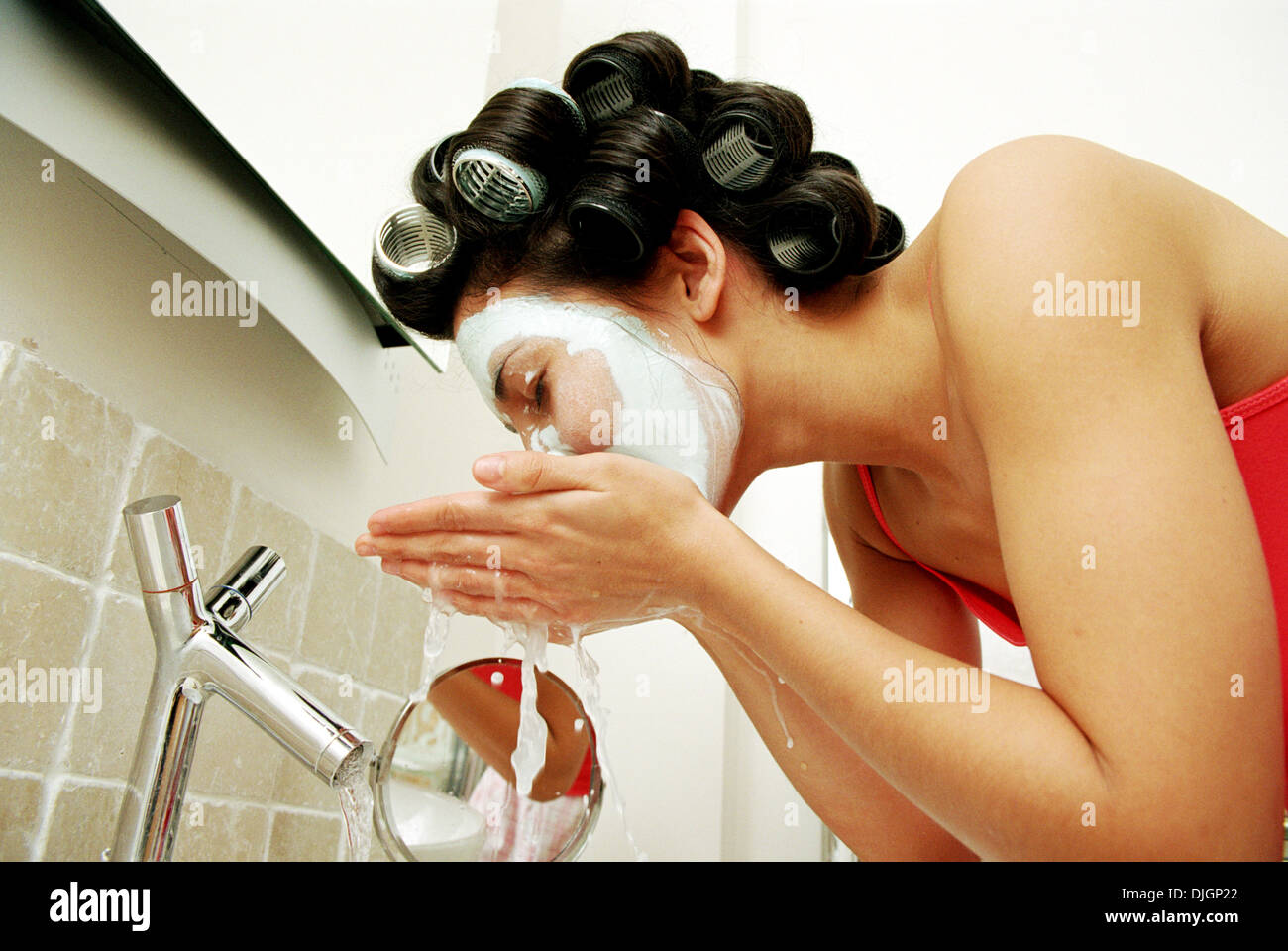 Woman Wash, Washing Off Face Mask Over Sink, Hair In Rollers, Skin Care