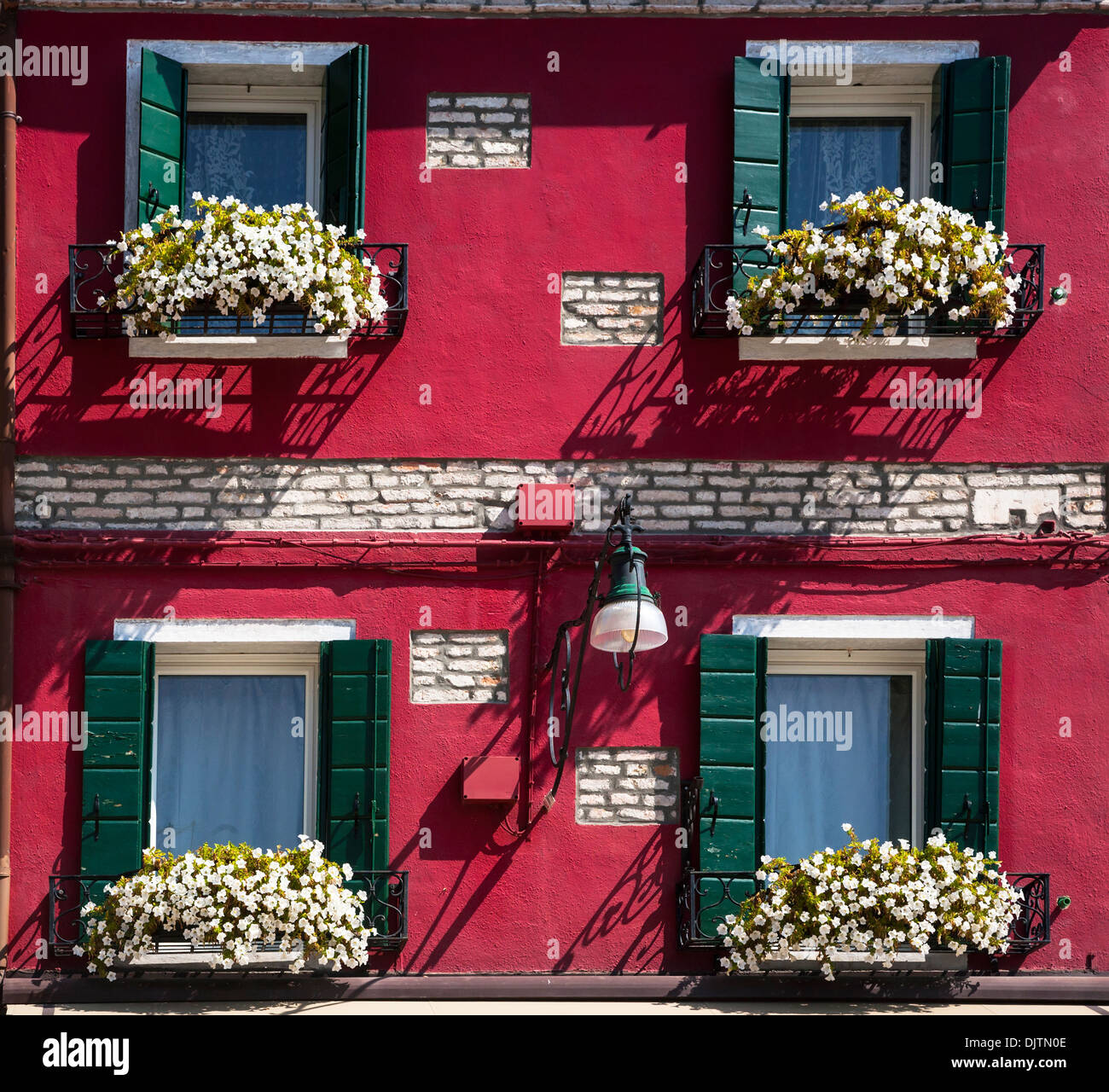 Red coloured house front with window boxes and flowers burano veneto italy