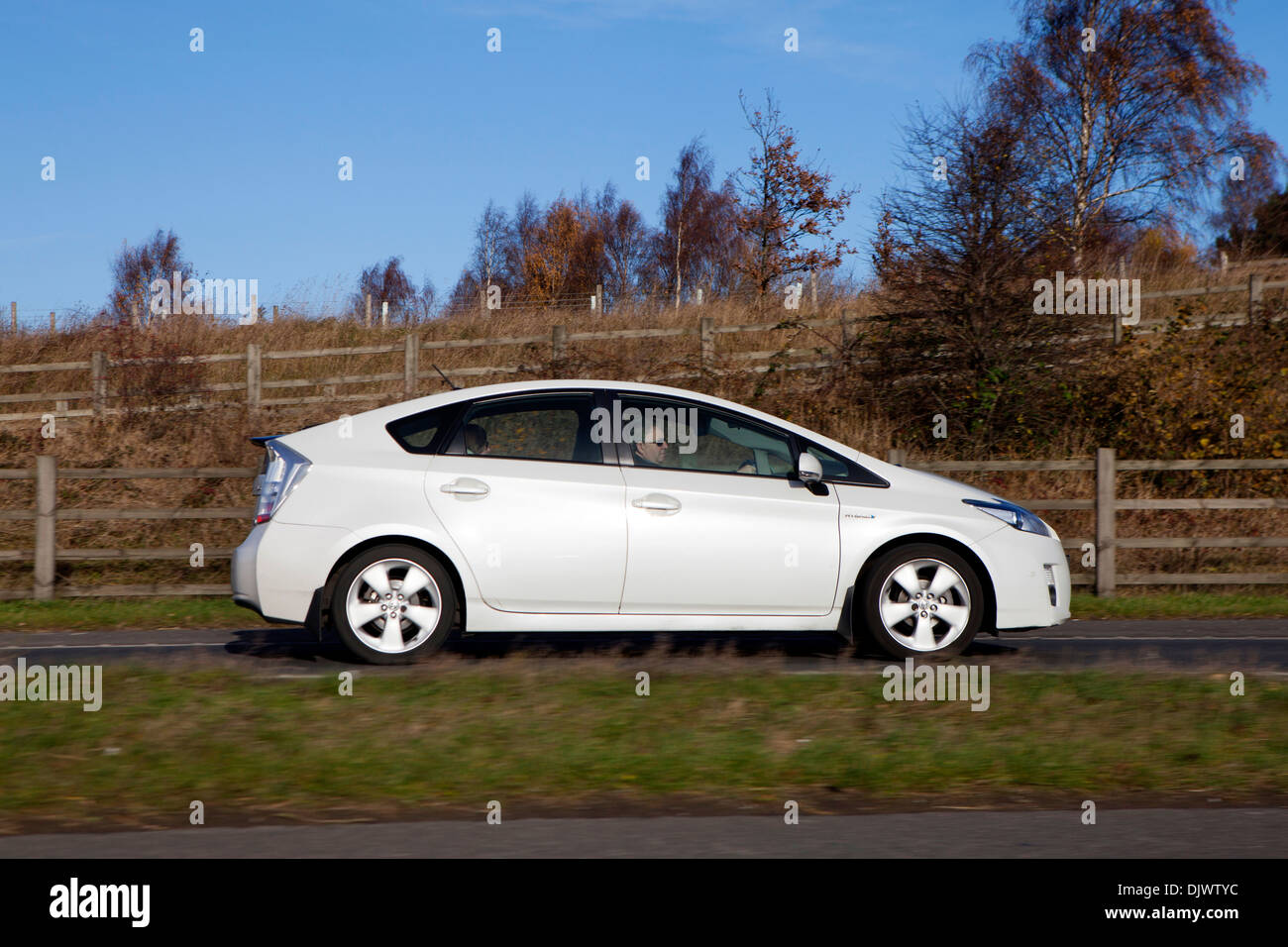 Stock photo white toyota prius full hybrid electric mid size hatchback side view driving on uk road