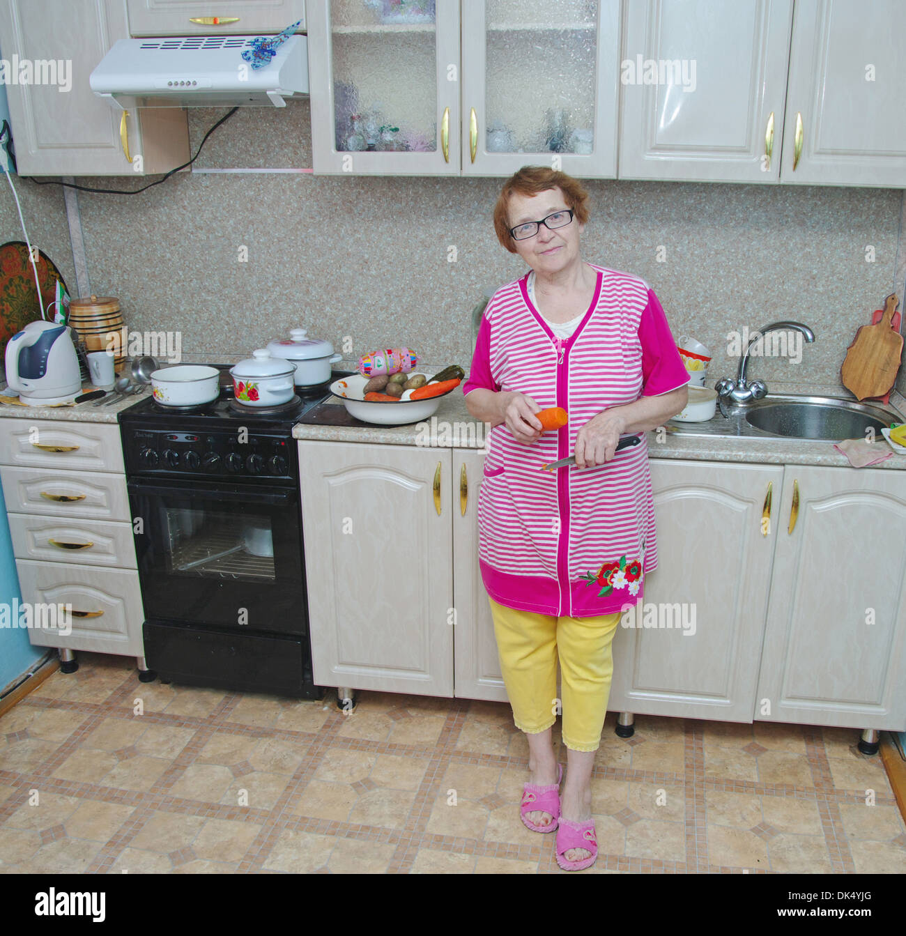 european elderly woman in the kitchen is a full length with a