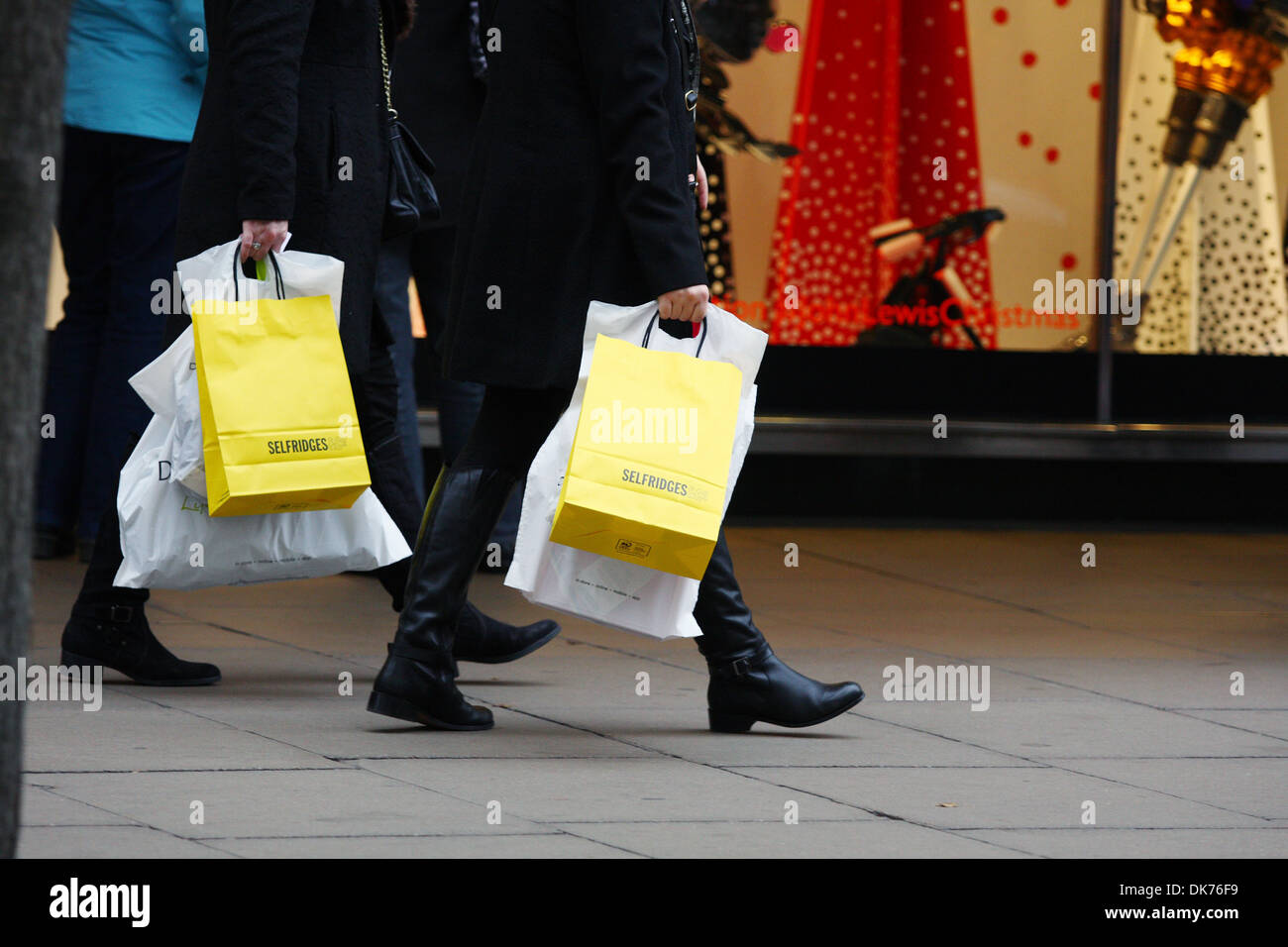 Part of two people carrying Selfridges and other shopping bags ...