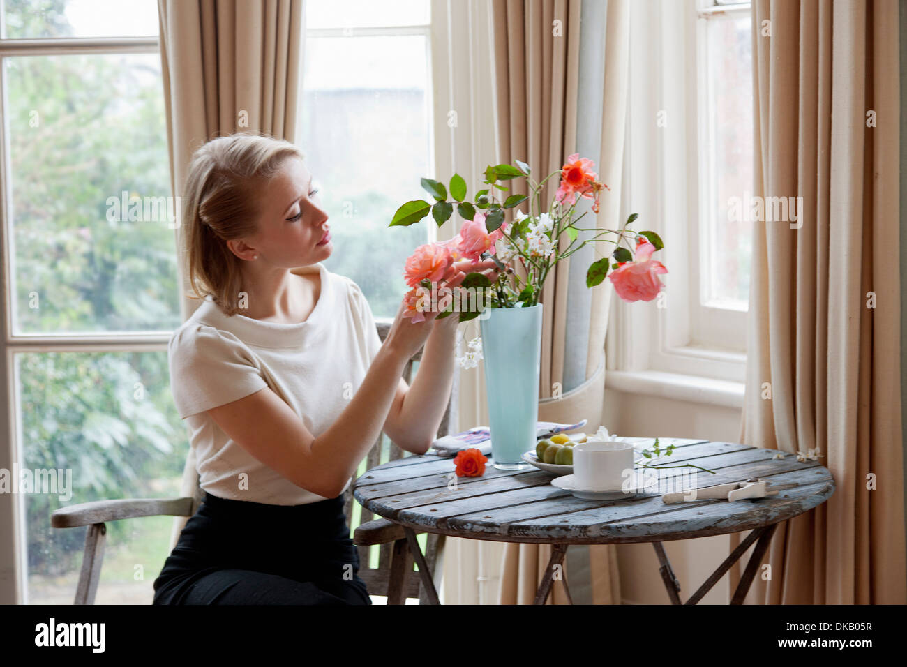 Woman arranging roses in vase stock photo 63551203 alamy woman arranging roses in vase reviewsmspy