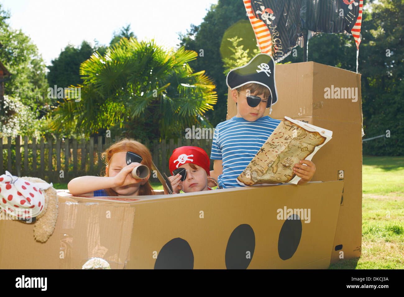 Stock Photo   Two Brothers And Sister Playing With Homemade Pirate Ship In  Garden
