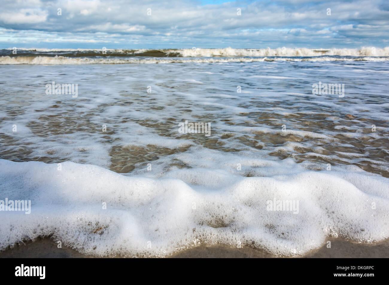 ocean waves spread thin foam laced sheets of water across the