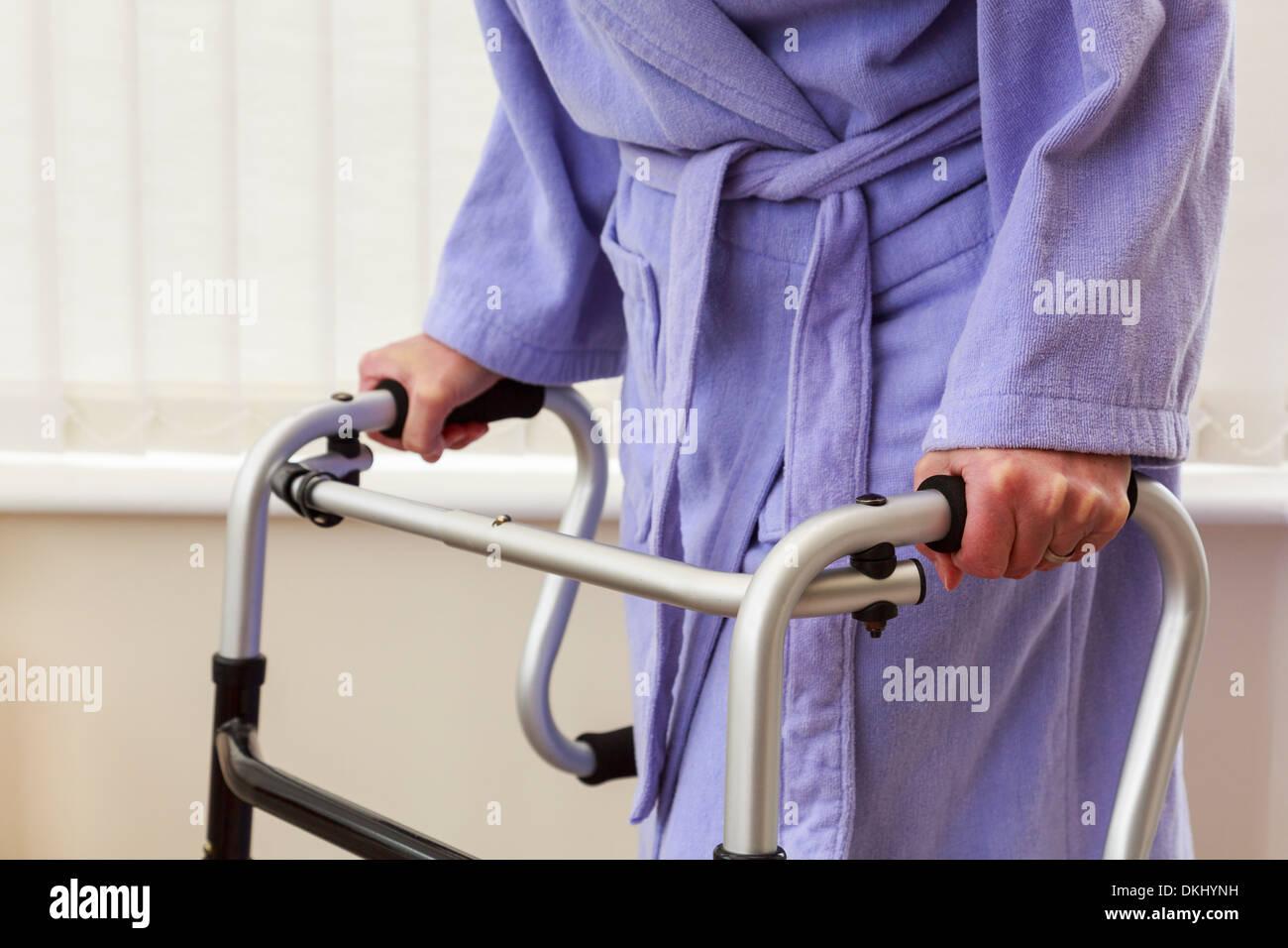 elderly senior woman older person wearing a bathrobe using a zimmer frame walker or support trolley - Zimmer Frame