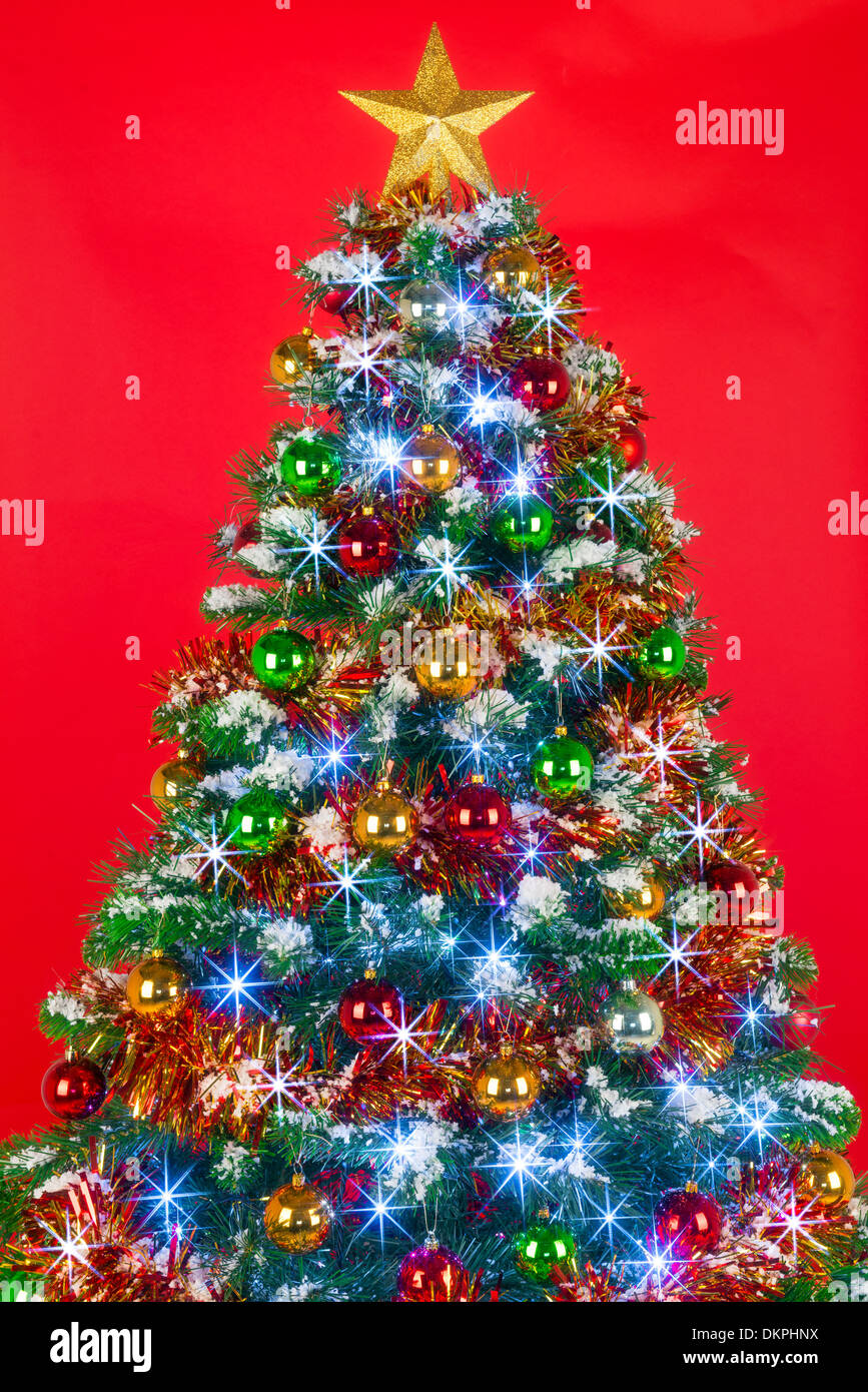 Christmas tree decorated with tinsel - A Decorated Christmas Tree With Baubles Tinsel And Fairy Lights Against A Red Background