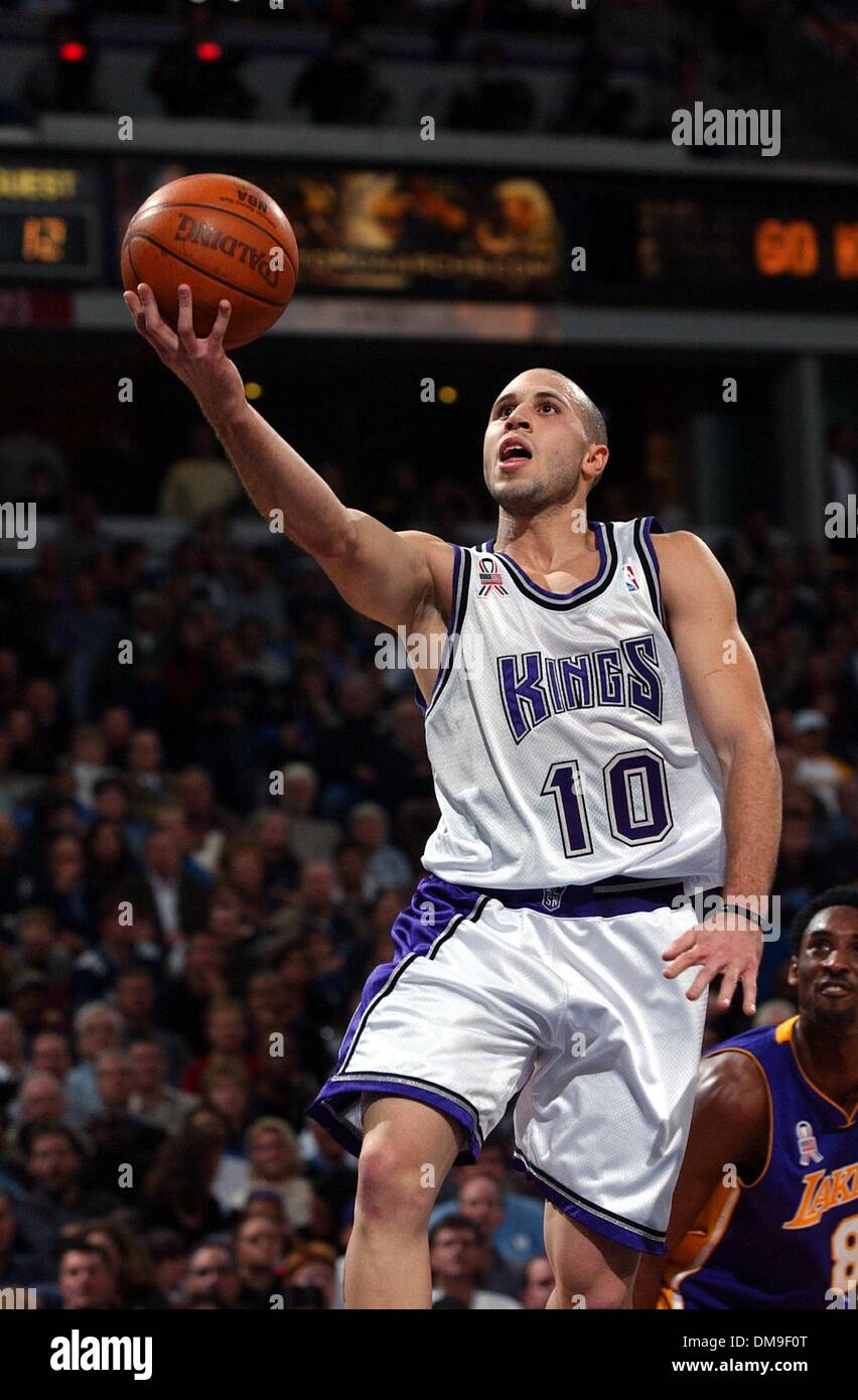 Sacramento King Mike Bibby slips past Kobe Bryant for two of his