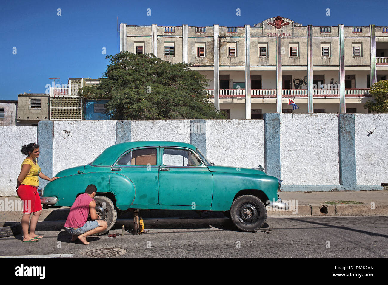 REPAIR OF AN OLD CAR IN FRONT OF A PRIMARY SCHOOL, STREET AMBIANCE ...