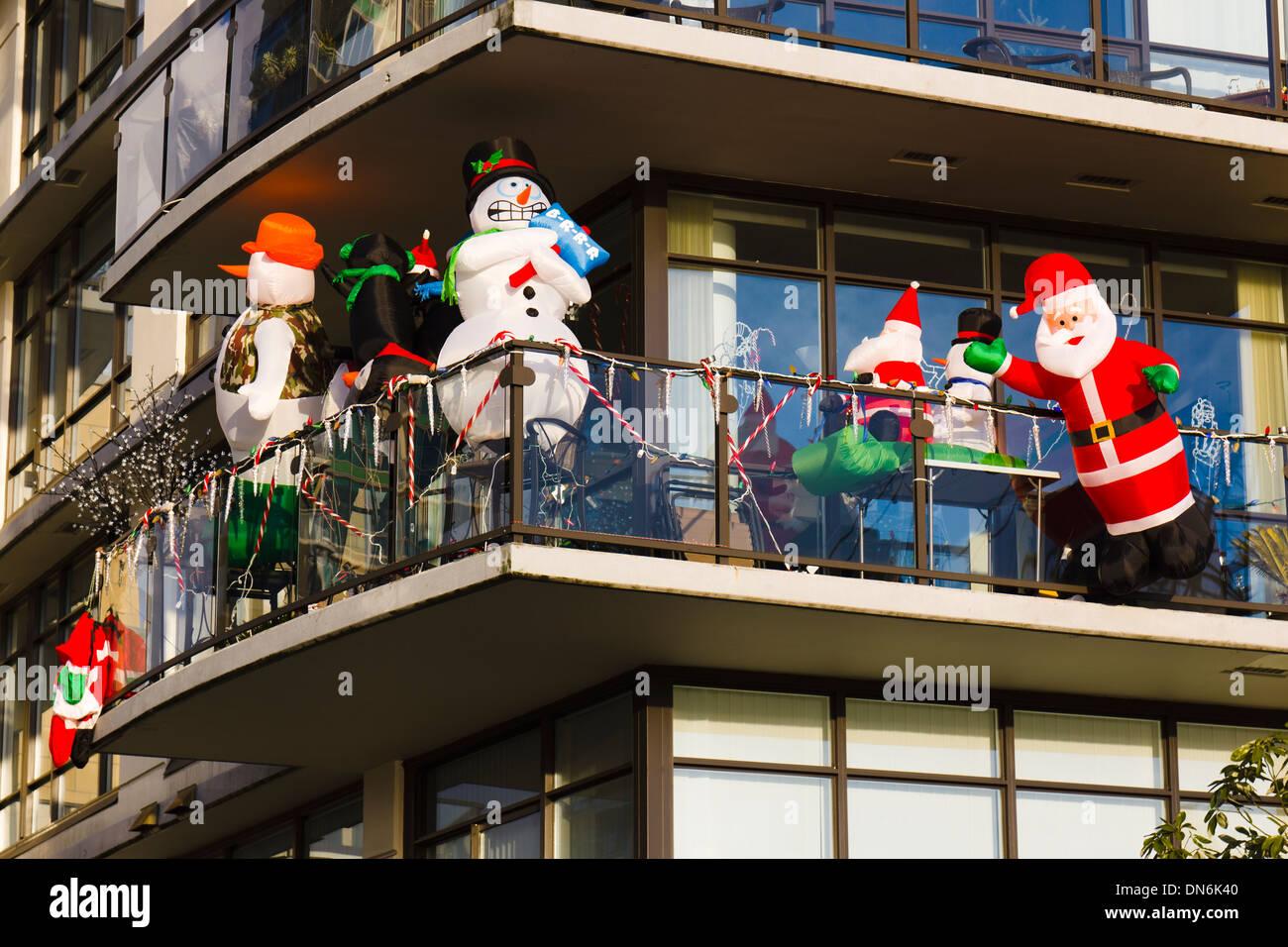 Inflatable Christmas decorations on a balcony. Snowman, Santa ...