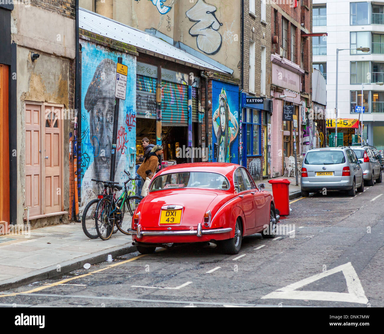 parked classic red car charlie burns street art and secondhand furniture shops in bacon street off brick lane east london uk