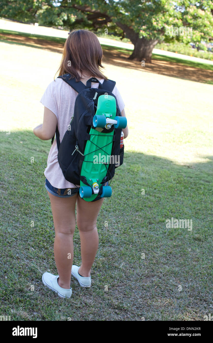 skateboard tied to backpack bag woman teen teenager skater ...
