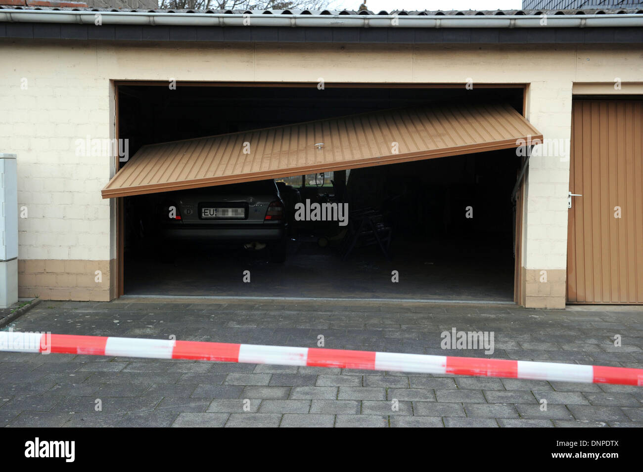 A garage door hangs damaged after the explosion of a World War II bomb in Euskirchen Germany 03 January 2014. A bomb from World War II & Euskirchen Germany. 03rd Jan 2014. A garage door hangs damaged ...